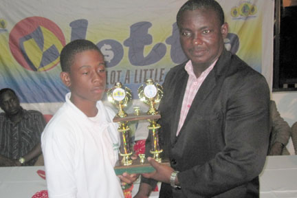 Grenada's Emmanuel Stewart, left,  receives a trophy from Parliamentary Secretary in the Ministry of Sports, Sen. Elvis Charles.