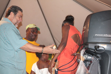 Fisherman of the Year 2013, Lenford Jack, receives an outboard engine, part of his prize, from Prime Minister Dr. Ralph Gonsalves. His daughter, Jayana, collect a trophy on his behalf from Miss SVG 2013 contestant, Brooke Legair.
