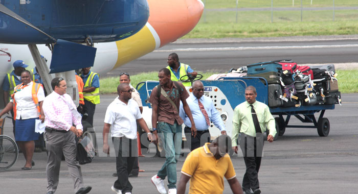Police escort Dwaine Sandy and his lawyer to the terminal building at the E.T. Joshua Airport.