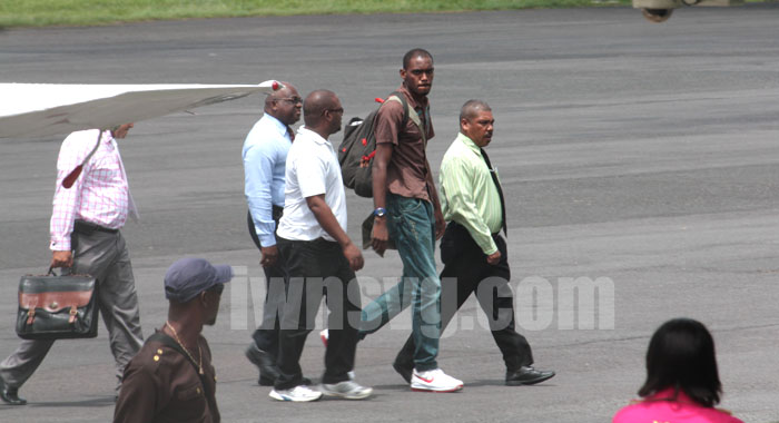 Dwaine Sandy (in brown) is escorted by police to the terminal building at the E.T. Joshua Airport shortly after arriving from Grenada on Monday, June 17, 2013. His lawyer, Grant Connell is furthers left and partly hidden. (IWN photo)