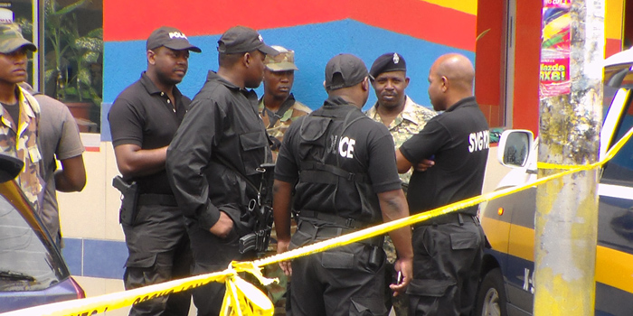 Member of the Rapid Response Unit (Black Squad) and the Special Services Unit talk at the scene where a police officer was shot on Thursday. (IWN photo)