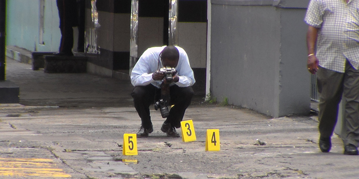 A police photographer work at the scene where a cop was shot in Kingstown on Thursday. (IWN photo)