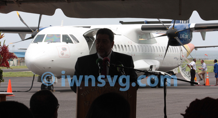 Prime Minister Dr. Ralph Gonsalves is a partial silhouette against the new ATR 72-600 aircraft as he addresses the welcoming ceremony on Wednesday. (IWN photo)