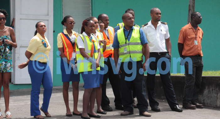 LIAT and other airport employees look on...