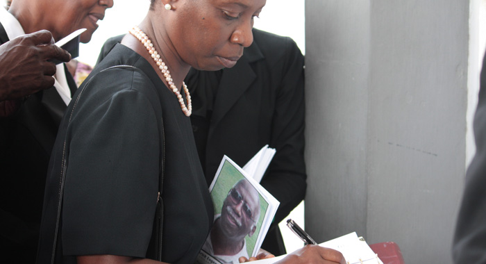 "A mourner passes signs a book of condolences at the funeral of Patrick ""Pat"" Prescod at the Kingstown Methodist Church on Thursday."