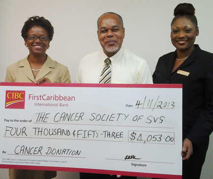 SVG Cancer Society's Sylvia Mapp receives cheque from monies raised for this year's Walk for the Cure from Country Manager Elroy John. Also pictured to John's left is Business Support Officer Jacintha Hinds.