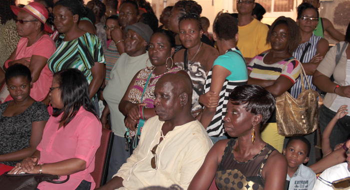 Acting Commissioner of Police, Michael Charles, seated centre, and other officials are pressed in as the crowd seeks shelter from the rain at the Prisons Concert. (IWN photo)