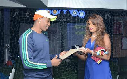 Dwayne Bravo, left, receives his history-making contracts from his Agent, Emma Everett on the eve of his signing to China Harbour.
