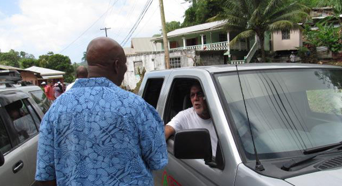 Opposition Leader, Arnhim Eustace, left, and Works Minister, Sen. Julian Francis, discuss the extent of the damage. (Photo: NDP)