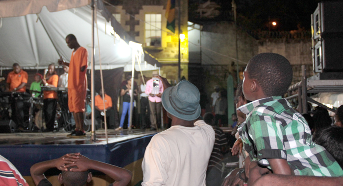 A young boy climbs up on a barricade to get a better view of the performances at the Prisons Concert. (IWN photo)