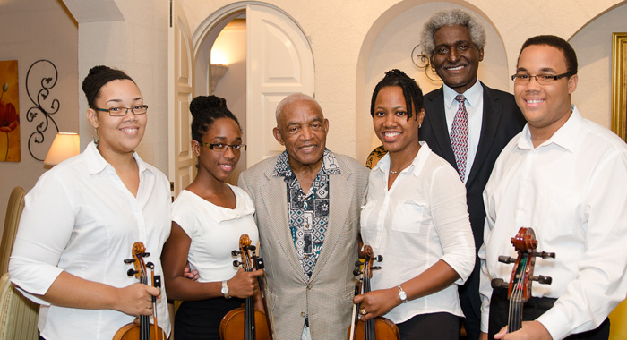 Irving burgie cocktail reception – Dr. Larry L. Palmer, U.S. Ambassador to Barbados, the Eastern Caribbean (far right) with Barbadian-American lyricist, Irving Burgie, centre, and members of the Barbados National Youth orchestra Katrina Nurse, Lora Toppin, Kaninie Knight and Dario Nurse.