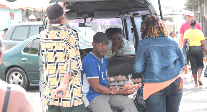A man sells eggs from the back of a van on Christmas Eve. The price of eggs soared to EC$20 a dozen. (IWN photo)