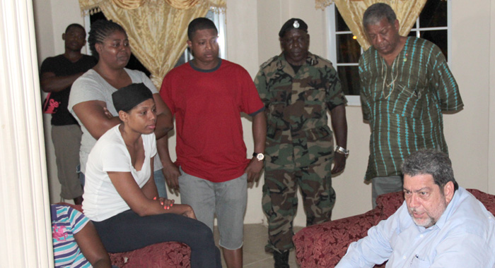 From right: PM Gonsalves, Prime Minister of Antigua, Baldwin Spence, and acting Commissioner of Police, Michael Charles, visit the family of disaster victim, Raymond Gonsalves. (IWN photo)