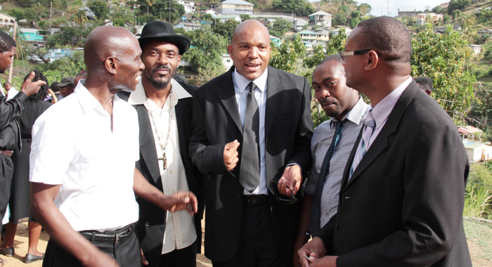 """""""THE POLITICIAN AND THE PRETENDERS"""": MP for South Leeward, Nigel Stephenson, centre, along with Unity Labour Party hopeful for that constituency, Sen. Jomo Thomas, left, and Financial Intelligence Unit Director Grenville Williams, right, chat with two teachers from the Buccament Bay Secondary School on the sidelines of the funeral service for murder victim Miranda """"Wiggy"""" Williams in Rillan Hill on Saturday, April 26, 2014. (IWN photo)"""