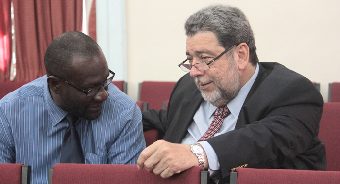 Prime Minister Ralph Gonsalves and Chief Immigration Officer Stanford Hamilton converse during the debate Monday morning. (IWN photo)