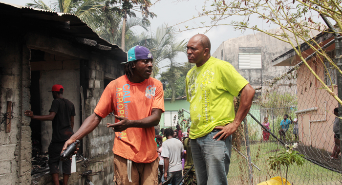 Stavius Diamond, left, chats with MP for South Leeward, Nigel Stephenson, outside the burnt-out house. (IWN photo)