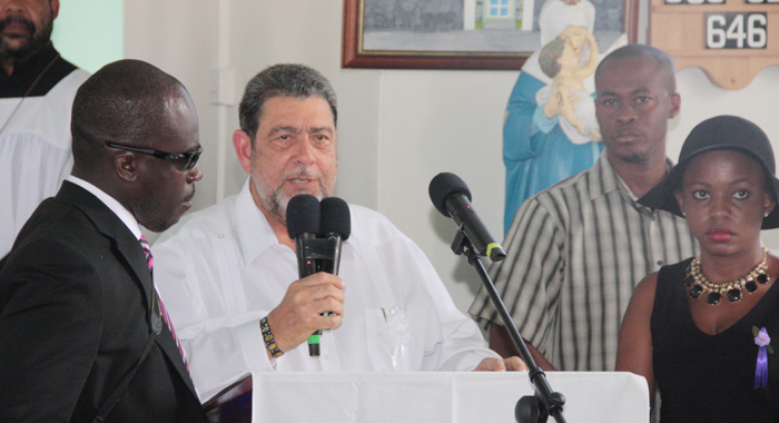 Prime Minister Gonsalves is flanked by two of Lynch's children, Keino Spring, left, and Shafia London, right, and a member of his security detail as he speaks at the funeral. (IWN photo)