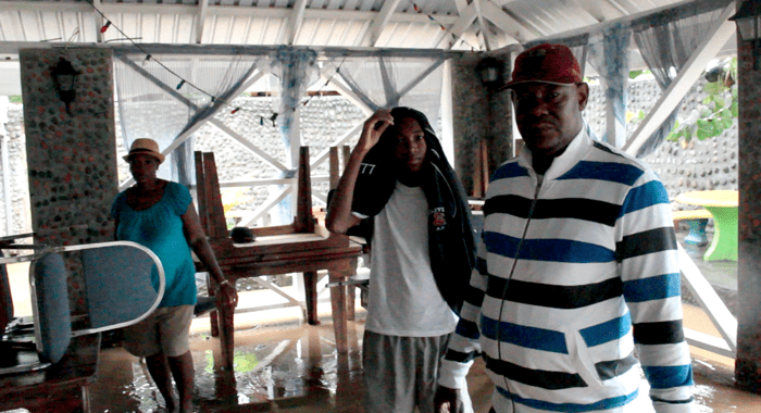 Jeffrey O'Garro and other members of his family stand inside their flooded business place. (IWN photo)