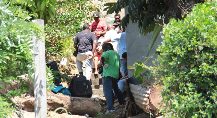 Detectives speak with Spence's relative at the scene in High Road, Barrouallie. (IWN photo)