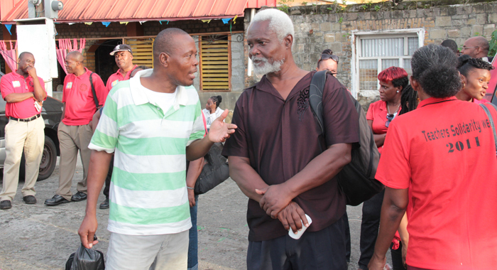Career educator Otto Sam, left, who is contesting in court his dismissal from the public service, chats with retired fellow educator Simeon Greene, on the sidelines of the rally on Friday. Greene was among the teachers who participated in the 1975 strike. (IWN photo)