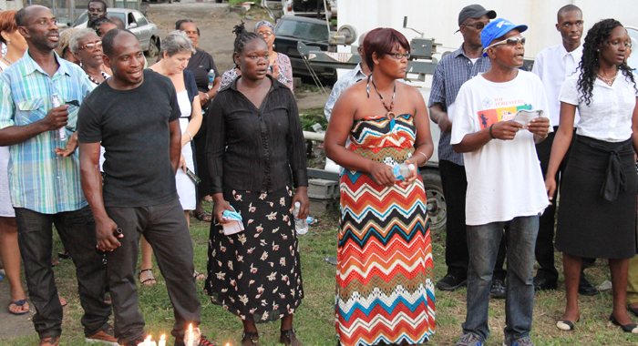 Hazell-Ann Jack, third left, whose daughter, Inka Jack, is missing after the floods, participate in the vigil on Wednesday.