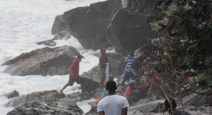 Civilians retrieve a body of one of the victims from the rough waters. (IWN photo)