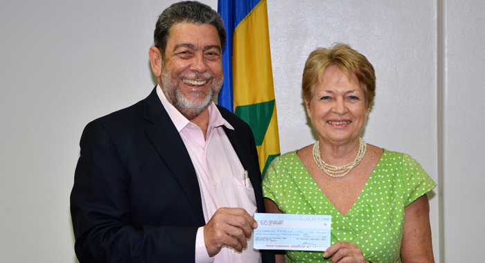 Lavinia Gunn, administrator of the Mustique Charitable Trust hands over a cheque for EC$100,000 towards the purchase of a school bus to Prime Minister Ralph Gonsalves.
