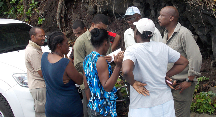 A police officer, in brown, collect information on the persons who were in the bus at Rock Gutter on Monday. (IWN photo)