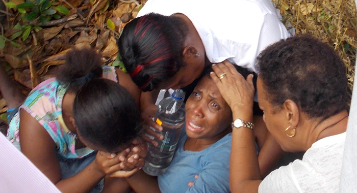 Persons react at the scene in Rock Gutter on Monday. (IWN photo)
