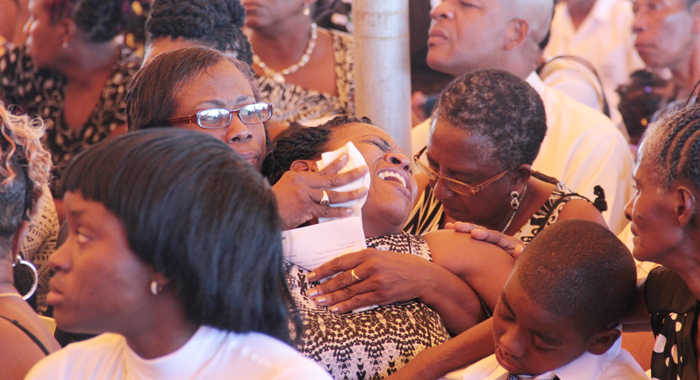 A woman is consoled as she weeps during the funeral service. (IWN photo)