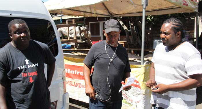 "President of NOBA, Anthony ""Code Red"" Bacchus, centre, inspects of the tickets given to minibus drivers Leroy Farrell, left, and Devon Bushay. (IWN photo)"