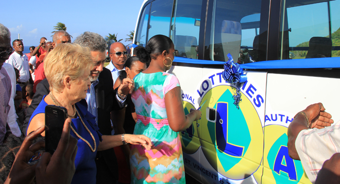 Fancy school bus 11 ribbon Jemma Edwards, who lost her sons, Jamalie and Jamall Edwards in the Rock Gutter incident, prepares to cut the ribbon, signalling the official commissioning of the new school bus. (IWN photo)