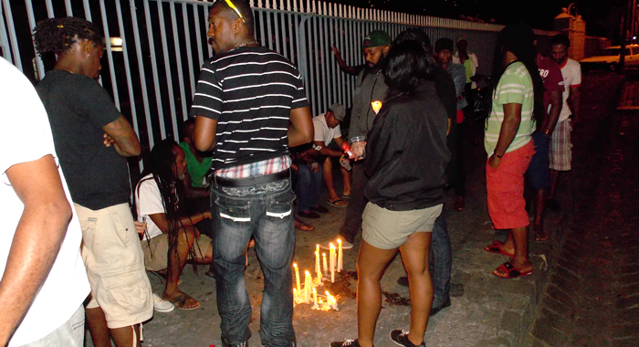 A number of persons participated in a candlelight vigil Sunday night at the scene of the collision the previous night. (IWN photo)