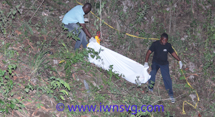Funeral home employees remove one of the bodies from along the embankment. (IWN photo)