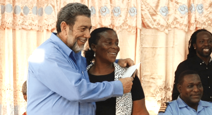 Prime Minister Dr. Ralph Gonsalves receives a postcard from parent Wendy Michael. (Credit: Image capture from API footage)