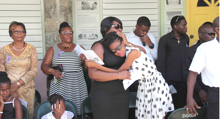 Women comfort each other at the funeral in Spring Village on Sunday. (IWN photo)