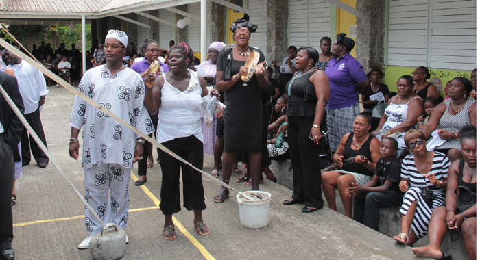 Persons beat tambourines and sing at the funeral in Spring Village on Sunday. (IWN photo)