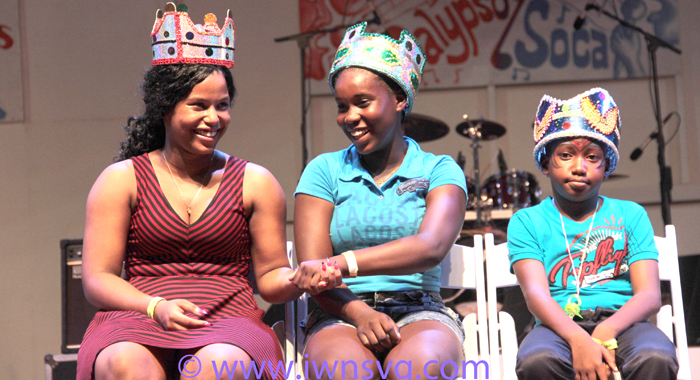 """Junior Soca Monarch Kelisa""""Singing Kelly"""" Barker of North Union Secondary, left, slaps hands with her schoolmate, Secondary School Calypso Monarch Ishanna 'Queen Shana' Phillips. Primary School Calypso Monarch Kristian Christopher is at right. (IWN photo)"""
