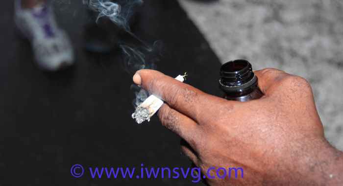 A man holds a marijuana cigarette in Kingstown during the Monday Street Party. (IWN photo)