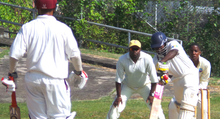 Desron Maloney batting in local cricket, closely watched by chairman of selectors Roland Wilkinson at first slip. (Photo: E. Glenford Prescott)