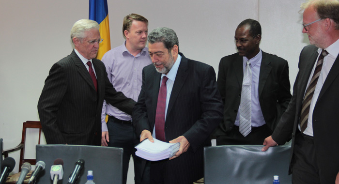 Prime Minister Ralph Gonsalves holds the three-volume business plan for SVG's geothermal power plant at the media launch in July. Gunnar Orn Gunnarsson, chief operating officer of Reykjavik Geothermal, is furthest right. (IWN photo)