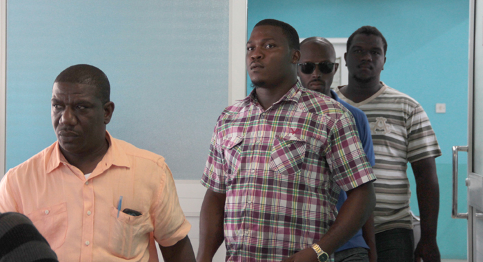 Lawyer Israel Bruce, left, burglary suspect, Kamorni Antoine, and police officer exiting the arrivals hall at the E.T. Joshua Airport on Sunday. (IWN photo)