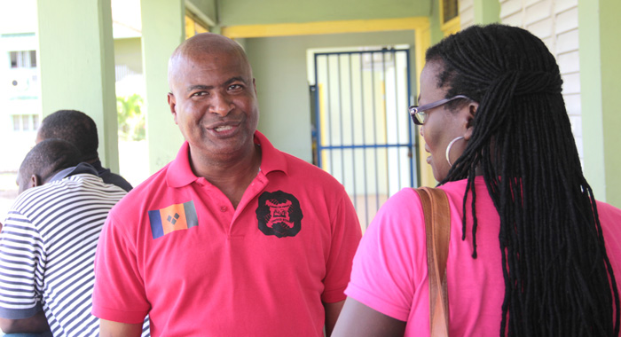 President of the Teachers' Union, Oswald Robinson, speaks with a union member after a meeting earlier this month. (IWN photo)