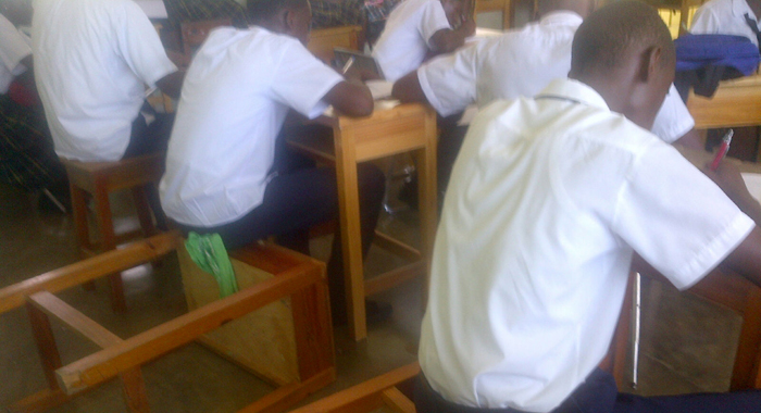 Students use desk as chairs at Petit Brodel Secondary School.