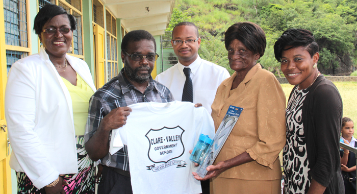 Cheryl Slater, mother of Kesha Slater-Latchman, does a symbolic handover of the items to head teacher Godfrey James. (IWN photo)