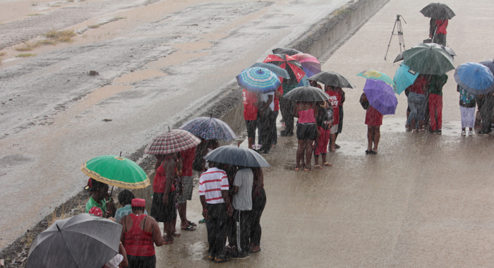 Persons shelter a heavy downpour as the await the arrival of the aircraft on Thursday. (IWN photo)