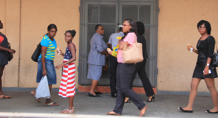 Persons walk by as the Supervisor of Elections, Sylvia Findlay is assisted by a police officer in locking up the Electoral Office on Wednesday. Some persons (not see in photograph) hurled insults at the official as she left for the day. (IWN photo)
