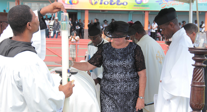 McIntosh's widow, Carmel, touches his casket at the funeral on Friday. (IWN photo)