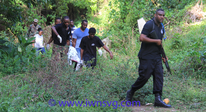 Police and funeral home workers return from the mountains with one of the bodies. (IWN photo)