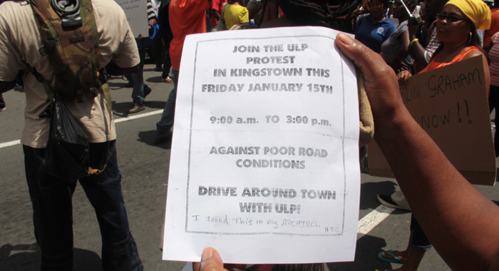 A protester on Friday holds a flyer that the ULP used during its activism 16 years ago. (IWN photo)